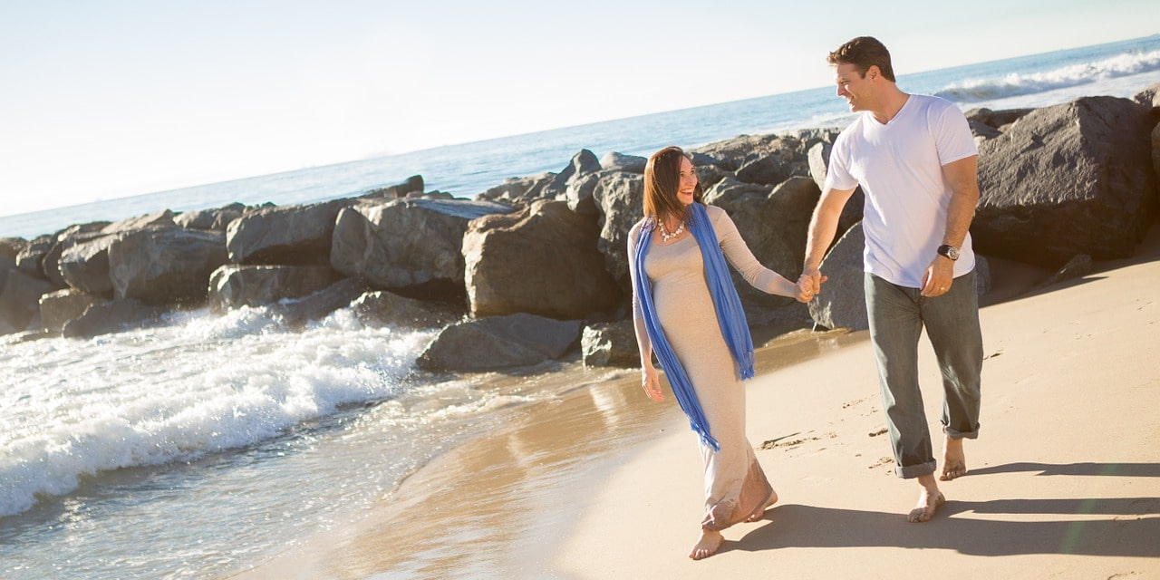 Молодая пара идет вдоль берега моря